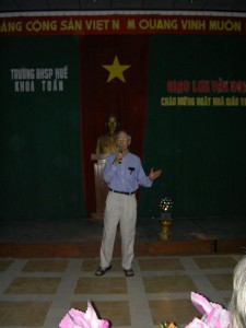 "Morgan sings ""The Mountains"" at Teacher's Day in Hue, with Ho Chi Minh presiding behind him."
